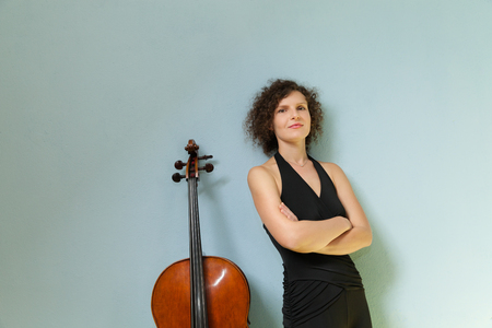 cellist: Portrait of young cellist, wall background