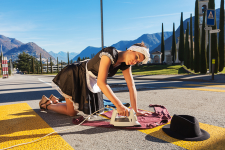 maid: Servicio de limpieza se extiende en la carretera en el paso de peatones Foto de archivo