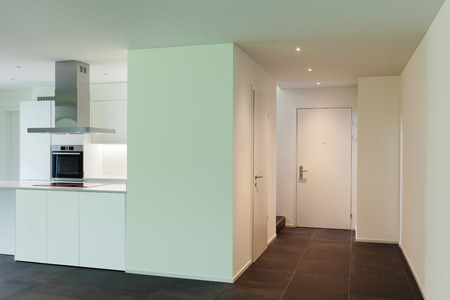 white door: interior of new apartment, view  entrance and domestic kitchen Stock Photo