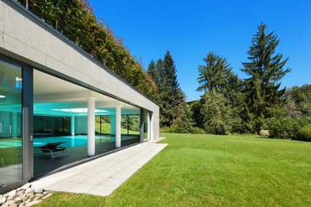 case moderne: Casa moderna, giardino con piscina coperta, all'aperto