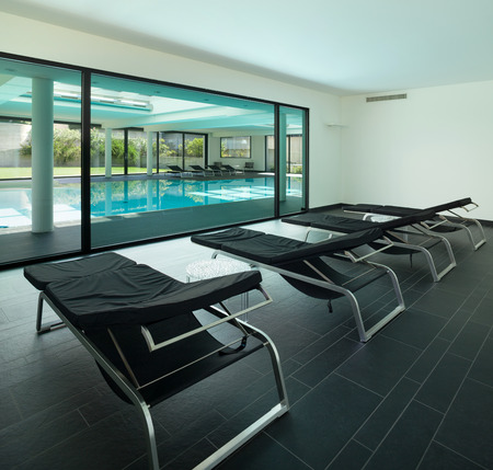 sunbed: indoor swimming pool of a modern house with spa, room with sunbeds