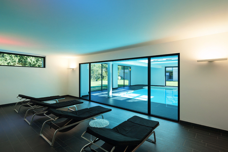 indoor swimming pool of a modern house with spa, room with sunbeds