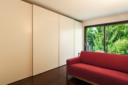 divan: Interior of modern house, room with closets and red divan