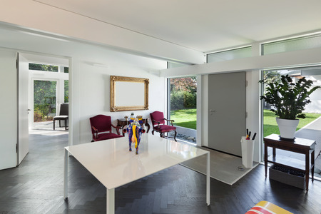 Architettura, spazio aperto di una casa moderna, soggiorno con tavolo e opere d'arte