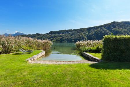 cielos abiertos: parque de una propiedad en el lago, dos hamacas Foto de archivo