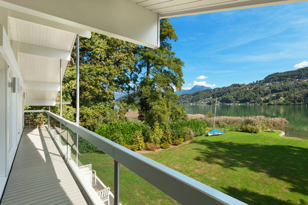 balcony view: long balcony of a modern house on the lake, park view