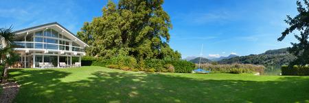 Vista di una bella casa con giardino verde, giorno d'estate Archivio Fotografico