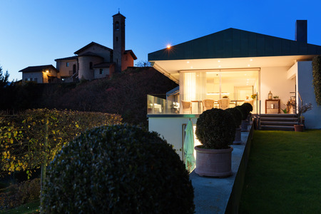 Beautiful modern house by night, view from the garden