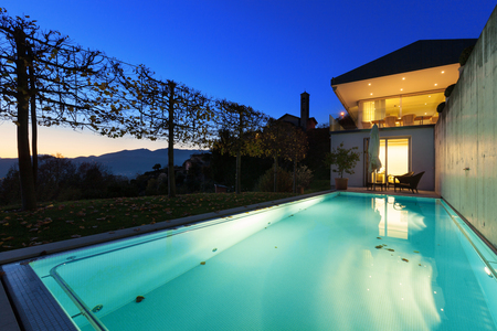 home exterior: Beautiful swimming pool of a modern house by night