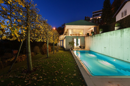 home exterior: Beautiful modern house by night, swimming pool