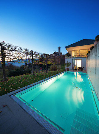 bienes raices: Beautiful modern house by night, swimming pool
