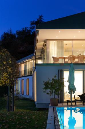 illuminated: Beautiful modern house by night, swimming pool