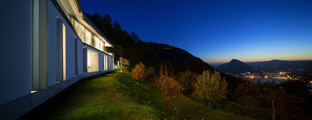 panoramic view: Beautiful modern house by night, view from the lawn