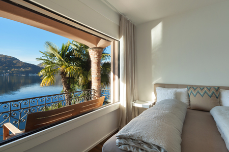 interior decor: Nice bedroom with large window, view of the lake Stock Photo