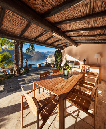 wood furniture: veranda of a classic house at sunset, wood furniture