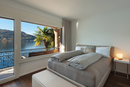 Nice bedroom with large window, view of the lake Stockfoto