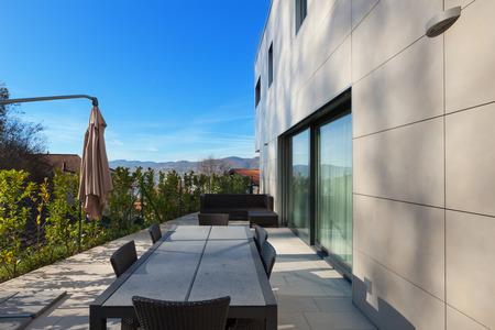 Hormigón: exterior de una casa moderna, patio con muebles de jardín Foto de archivo