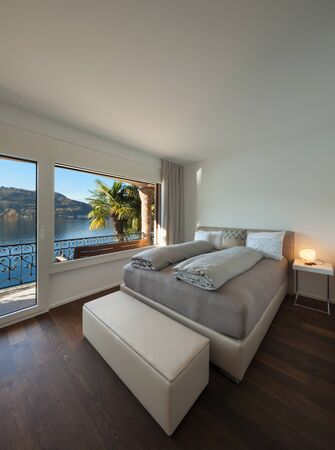 window view: Nice bedroom with large window, view of the lake Stock Photo