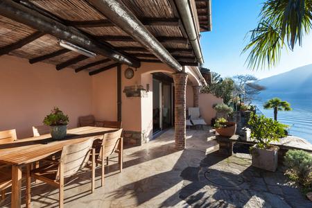 veranda: veranda of a classic house at sunset, wood furniture