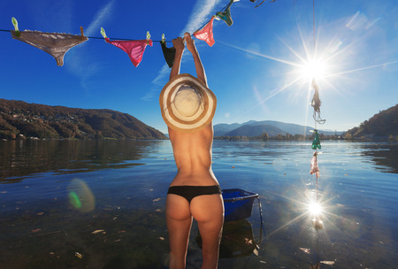 nude nature: Girl hanging clothes by the lake Stock Photo