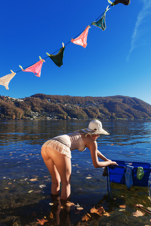 naked women: Girl hanging clothes by the lake Stock Photo