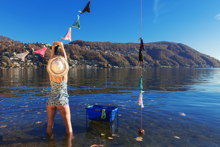 sexy women naked: Girl hanging clothes by the lake Stock Photo