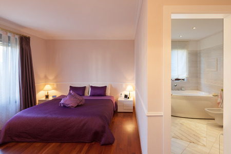 bedroom of a modern apartment, double bed with purple bedspread Stockfoto