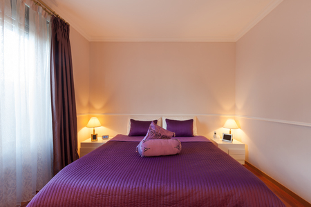 double bed: bedroom of a modern apartment, double bed with purple bedspread Stock Photo