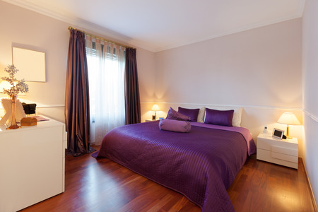 bedroom bed: bedroom of a modern apartment, double bed with purple bedspread Stock Photo