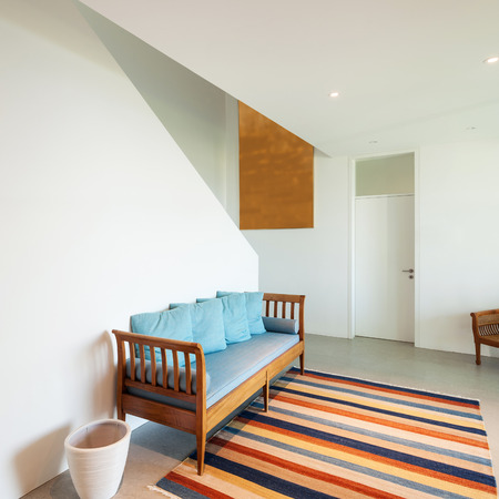 divan: Interior of a modern house, hall with divan and striped rug
