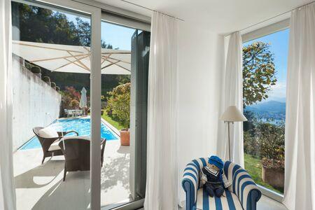 cielos abiertos: Interior of a modern house, window with access to the pool Foto de archivo