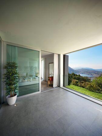 ventana abierta interior: Interior de una casa moderna, balc�n con vista al lago