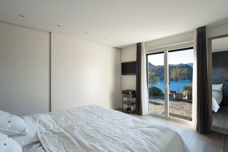 view of a comfortable bedroom: Interior of house, comfortable bedroom, view from the bed Stock Photo