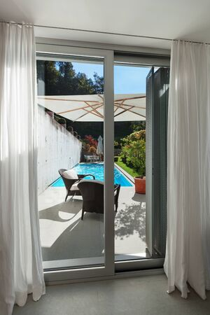 cielos abiertos: Interior de una casa moderna, ventana con acceso a la piscina Foto de archivo