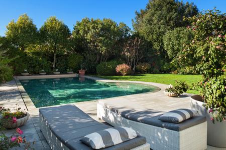 Bellissimo giardino con piscina, due lettini prendisole Archivio Fotografico