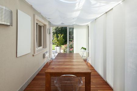 silla de madera: terraza con cortinas blancas y mesa de madera