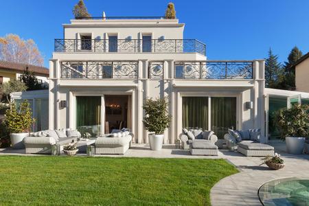 mooi huis met zwembad, blauwe lucht en de weelderige tuin Stockfoto