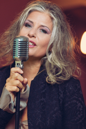 mature women: portrait of mature female singer with microphone
