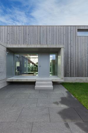 Entrada de una casa moderna en el hormigón y madera, exterior Foto de archivo - 56030589