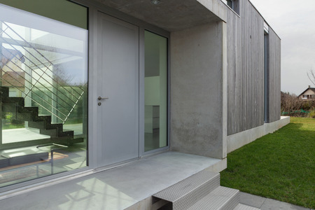 Entrance of a modern house in concrete and wood, outside Stok Fotoğraf - 56030594