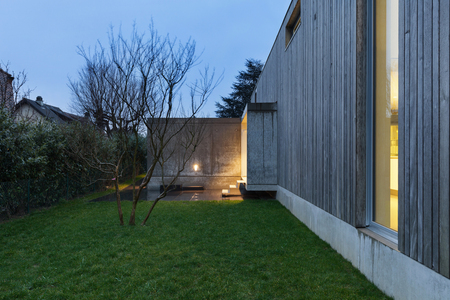 contemporary house: Entrance of a modern house in cement and wood, evening