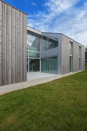 wood lawn: Exterior of a modern house in cement and wood, lawn