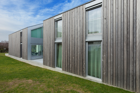 wood lawn: Exterior of a modern house in concrete and wood, lawn