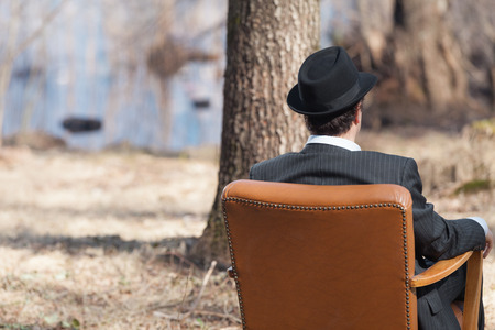 rear view: man alone in the woods sitting on a armchair, rear view
