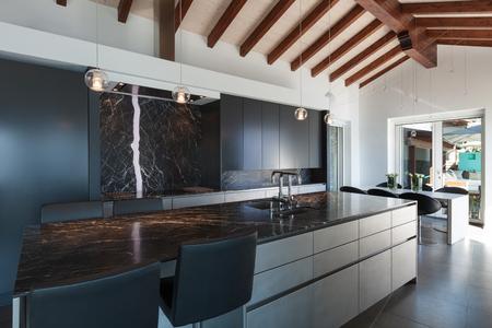 Interior de un altillo, cocina con encimera de mármol, diseño moderno Foto de archivo - 56030147