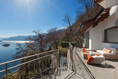 div�n: Terrace with comfortable divan and lake view, outdoors Foto de archivo