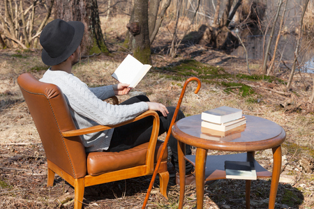 man sit: young man reads a novel in the woods Stock Photo