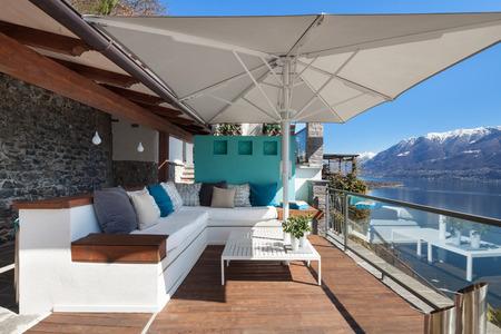 Salon taras z wygodnymi divans i widokiem na jezioro w luksusowym domu