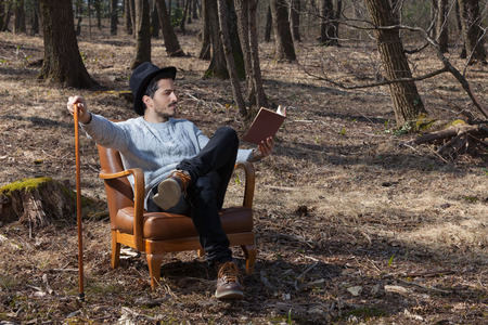 novel: young man reads a novel in the woods Stock Photo