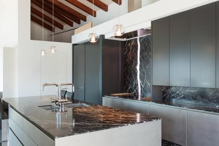 Interior de un altillo, cocina con encimera de mármol, diseño moderno Foto de archivo - 56029922